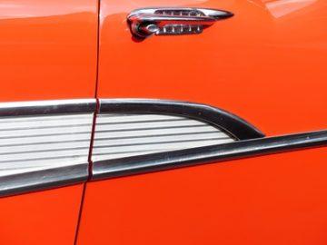 Trgriff und Chromverzierung einer hellroten amerikanischen Limousine der Fuenfziger Jahre